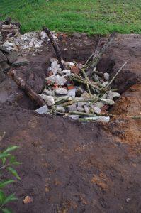 Bauphase einer Reptilienburg: Ein ca. 1,5 m tiefes Loch wird mit Bauschutt und Holz verfüllt
