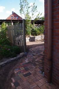 Übergang von Betonpflasterung zu Buntem Pflaster aus Naturstein, Klinker und Beton.