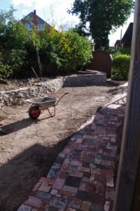 Pflaster aus verschiedenen Steinen und Betonbruch-Trockenmauer
