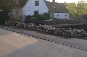 Trockenmauer zur Grundstückseinfriedung mit Sitzsteinen, Bauphase.