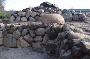 Trockenmauerterrassen mit Feldsteinen, einem Sitzstein und Steinhaufen. Ausmagerung mit Kies - Bauphase